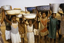 Vodu nosí ženy a výhradně v nádobách na hlavě (Ghana).