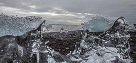 Severní ledový oceán poblíž ledovce Breiðamerkurjökull, ze kterého se odtrhávají ledové kry, sesunují se na vodní hladinu jezera Jökulsárlón a směřují k moři, kde je vlny vyvrhují zpět na pevninu.