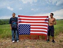 Oglalští mladíci drží vlajku vzhůru nohama. Je to mezinárodní symbol strádání a projev odporu vůči vládě Spojených států. Snímek vznikl na vzpomínkovém shromáždění, jehož účastníci si připomněli přest