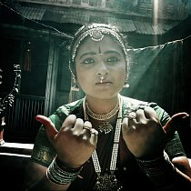 Teja má na sobě tradiční tamilské nařasené sárí v kontrastních barvách zelené a červené s okraji zdobenými zlatě.