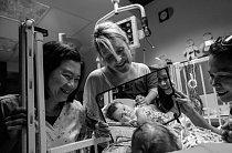 Nanovorozeneckém oddělení intenzivní péče Texaské dětské nemocnice vHoustonu se pětiměsíční Lucas Guidry pozoruje vzrcátku, které mu přidržuje jeho maminka Sydney (uprostřed). Dětem předčasně narozeným nebo nemocným hrozí riziko opoždění vývoje.