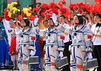 Tři čínští astronauté (zleva: Liu Yang, Liu Wang a Jing Haipeng) před vesmírnou cestou zdraví před odletem 16. června 2012.