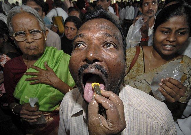 Fotografie zachycuje muže, jak se právě snaží polknout živou rybu. Každý rok na začátku léta se v Hajdarábádu v jižní Indii srocují lidé na místním stadionu k rituálu pojídání živých ryb. Ten jim má p