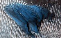 Písek se hromadí do dun na dně marsovského kráteru Lyot, jak jej na snímku zachytila sonda NASA Mars Reconnaissance Orbiter. Tato duna se ve zvýrazněných barvách zdá světle modrá, protože se její zrnka liší velikostí a složením od okolních sedimentů.