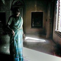 Náhle uslyším jemné cvaknutí dveří, kterými tiše do tmavého pokoje projde stará žena v modrém sárí.  Zasněně se zahledí na taneční kreace. Možná se jí hlavou honí vzpomínky na doby minulé, kdy i ona
