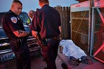 Muž z Minnesoty (pod prostěradlem), který měl zánět plic, zkolaboval a zemřel před jednou čerpací stanicí ve Watford City.