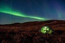 Stan stojící nedaleko mezinárodního letiště Kangerlussuaq. Vedle polární záře je možné si všimnout laserového paprsku mířícího ze zdejší vědecké stanice Kelly Ville do ionosféry. Pomocí tohoto laseru