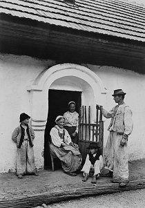 Slovenská rolnická rodina ve svém běžném oděvu Povšimněte si oblouku v normanském stylu, který je pro slovenské domy typický. Povšimněte si také třásní dole na kalhotách, které jsou dosti široké opro