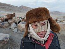 Mladý pastevec má na obličeji improvizovanou masku, která ho chrání před extrémním zimním chladem.