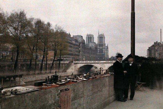 Dva muži stojí u drobností prodávaných na nábřeží Seiny ve dvacátých letech minulého století, s katedrálou Notre Dame v pozadí.