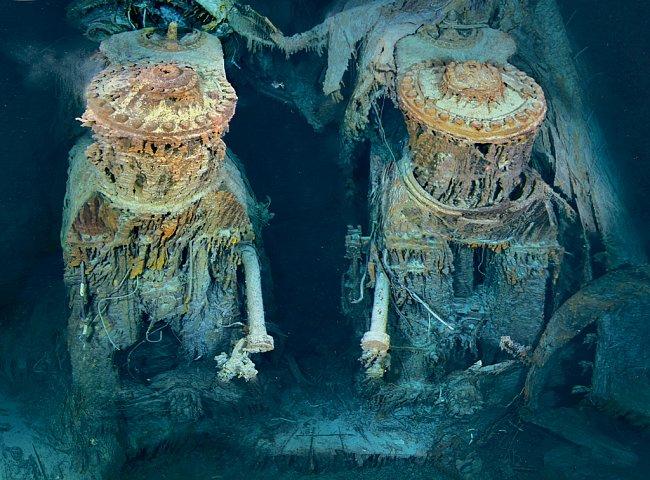 """Zející otvor na zádi plavidla odhaluje dva z jeho motorů. Obrovské stroje vysoké jako čtyřpatrový dům kdysi poháněly Titanic. Dnes je pokrývají oranžové kovové """"rampouchy"""" vzniklé činností bakterií, k"""
