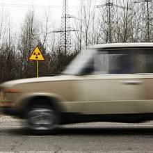 Auto projíždí radioaktivní zónou blízko elektrárny. Problémem jsou lesní požáry, které nadále šíří radioaktivní částice do vzduchu.
