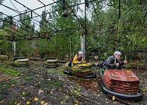 Studenti zFinska, kteří mají pro pobavení ikvůli ochraně před deštěm nahlavě helmy zalobalu, pózují vautíčkách vzarostlém zábavním parku.