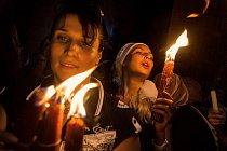 Pravoslavní křesťanští poutníci z východní Evropy si s nadšením připalují svíčky od svatého ohně, který se podle tradice den před Velikonocemi rozhoří z Ježíšova hrobu v jeruzalémském chrámu Božího hrobu.
