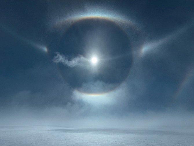 Soustava prstenců, kruhů a dalších halových jevů zářících nad ledovým příkrovem Grónska. Tyto jedinečné úkazy způsobuje lom slunečního světla na ledových krystalcích, které víří vsilném větru, nazývaném vGrónsku piteraq.