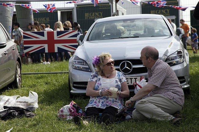 Co lidé dělají? Sedí, jedí, pijí a dobře se baví. Je to rodinný a společenský day out, byli na dostizích, zůčastnili se prvního dne oslav 60. let Alžbětina panovnictví v přítomnosti samotné oslavenkyn