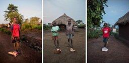 Peter Mandela (vlevo), Wane Samuel a Cosmas Amule (uprostřed) a Joghua Burkene (vpravo) pózují v Bidi Bidi s vlastnoručně vyrobenými kartonovými nákladními i osobními auty. Většina obyvatel tábora jsou děti.