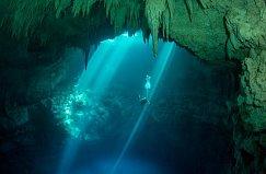 Potápěč sestupuje do cenote (krasová průrva zatopená vodou) v Mexiku. Výzkum cenotů umožňuje archeologům objevit nové klíčové poznatky o mayské civilizaci.