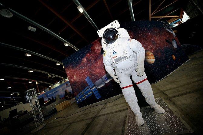 Americký skafandr EMU pro výstup mimo mezinárodní kosmickou stanici ISS a pro práci ve volném prostoru. Vpozadí je na rozměrném panelu představa smělých plánů výprav nových amerických lodí Orion do hlubin naší sluneční soustavy.