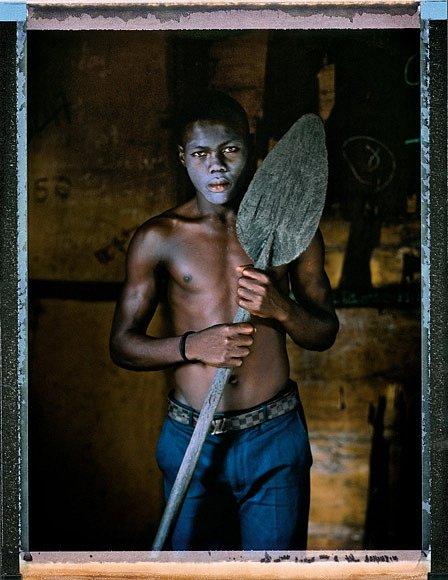 """Šestnáctiletý rybář Monday Enikanoselu se narodil ažije vMakoku, chudinské čtvrti přiLagoské laguně. Natírá si obličej krémem naekzém anosí pásek sfalešnou značkou Louis Vuitton. """"Lagos kemně bude hodný,"""" říká. """"Lagos nám všem přinese užitek."""""""