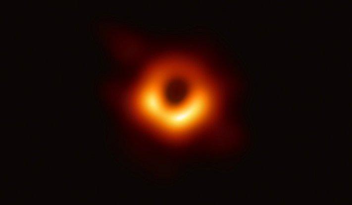 Astronomové z mezinárodního týmu ukázali historicky první fotografii černé díry. Nachází se v centru galaxie Messier 87 v souhvězdí Panny a od naší soustavy je vzdálená 55 milionů světelných let. Váží tisíckrát víc než černá dírná díra v naší Galaxii.
