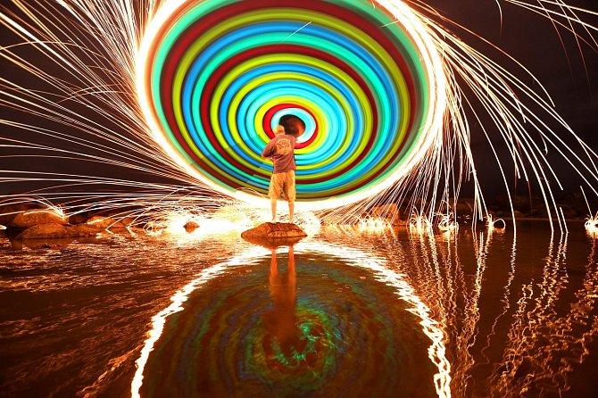 Chris Brady (53) z Kalifornie vytváří ohnivá duhová kola pouhým roztočením zapálené ocelové brusné vlny. Svoje umění předvedl na pláži ve městě Coronado.