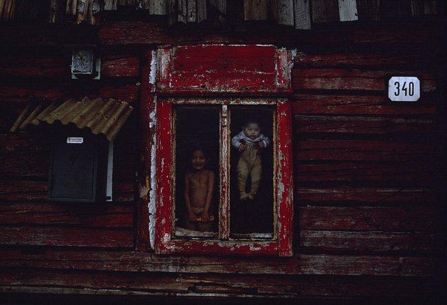 Za oknem na špatné adrese ukazuje matka své děti v romské osadě u východoslovenské Richnavy. Za komunistické vlády urbanizovaní, nicméně neasimilovaní Romové, jak si cikáni říkají, jsou často první, k