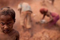 """Ti menší vybírají z cihelného prachu černé zlato (drobné """"valouny"""" uhlí), které se dá prodat a ony tak přispějí svým rodinám na živobytí."""