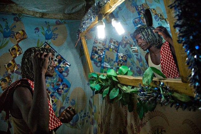 Afarský švihák si v místním verzi obchodu s kosmetikou kontroluje v zrcadle kadeře ztužené velbloudím mlékem. FOTO: John Stanmeyer