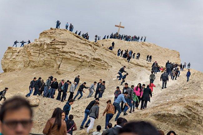 Během týdenní slavnosti Zjevení Páně stoupají kousek od břehu Jordánu arabští křesťané ke kříži, aby se pod ním pomodlili.