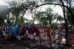 Ženy a děti se brodí vodou a bahnem, aby si naplnily své kanystry u distribučního místa pitné vody v táboře Batil. Silné deště a záplavy v táboře zhoršily už tak špatný stav vodních zdrojů a sanitace.