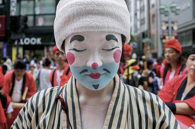 Japonsko: Žena oblečená jako čondara, tradiční klaun z japonského ostrova Okinawa, se účastní jedné z mnoha pouličních slavností v Tokiu.