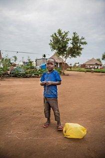 Malý chlapec si hraje s plastovou taškou přivázanou na šňůrce.