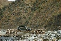 Snímek zachycuje nosiče, jak přenášejí auto přes řeku v Nepálu.