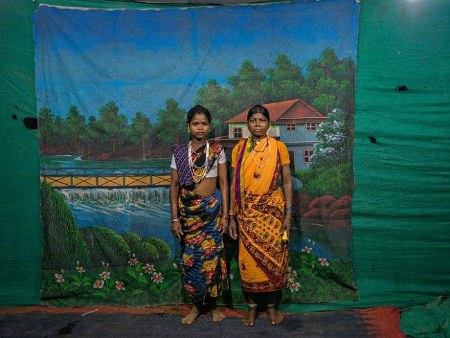 Domorodé ženy stojí před namalovaným pozadím navýroční slavnosti vevesnici Órčha vzalesněné oblasti Abudžmarh vestátu Čhattísgarh. Oblast je hlavní základnou maoistických povstalců – naksalitů.