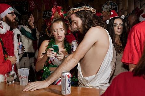 Dva návštěvníci baru převlečení za Ježíše Krista a Cindy Lou popíjejí a vyměňují si telefonní čísla během předvánočního setkání Santů ve Scottsdale vArizoně vroce 2016.