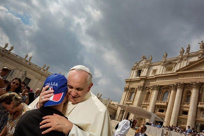 Papež František objímá zdravotně postiženého mladíka před bazilikou svatého Petra. Vůdce 1,2 miliardy křesťanů je obdivován pro svou vřelost, otevřenost askromnost.