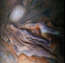 """Velkolepé mraky víří jako inkoust v Jupiterově Severním mírném pásu, zde pozorovaném sondou NASA Juno. Pohled obsahuje bělavé """"vystupující"""" mraky a bílý ovál, což je jistý druh anticyklonové bouře, která je menším příbuzným Jupiterovy Velké rudé skvrny."""