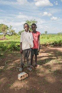 Dva chlapci si na volném prostoru v Bidi Bidi hrají s ručně zhotoveným náklaďákem.