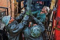 Naftaři stojí na plošině a odstraňují tři kilometry těžkého ocelového vrtacího potrubí po částech dlouhých 9,75 metru, zatímco se z vrtu tlačí na povrch ropa a zemní plyn.