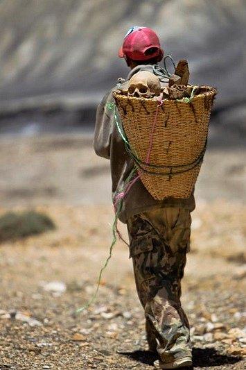 Muž z bývalého království Mustang v severním Nepálu přenáší lidské pozůstatky objevené v pohřební kryptě.