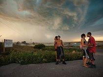 Mládež postávající na okraji městečka Wounded Knee nedbá na blížící se letní bouřku. Nedaleko odtud – bylo to 29. prosince 1890 – zabili vojáci americké armády nejméně 146 indiánů. Pro Siouxe a ostatn