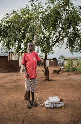 Desetiletý James Lokusan tahá po hrbolaté prašné cestě v Bidi Bidi svůj kartonový náklaďák.