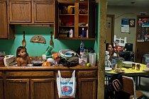 Tříletý C. J. Shot se koupe mezi nádobím. V souladu s představou Oglalů o tiospaye – jednotě a spolupráci členů rozšířené rodiny – jsou jejich domovy často přelidněné. K tomuto stavu přispívá i kritic