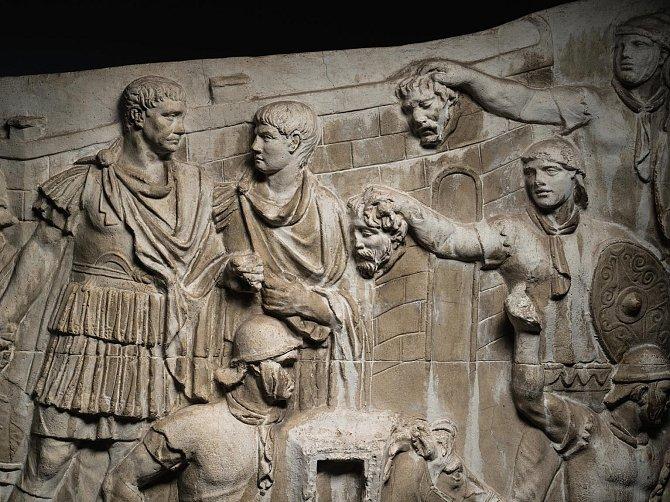 Vtéto scéně naodlitku ze sádry a mramorového prachu, vytvořeného mezi roky 1939a 1943, pozoruje Traianus (zcela vlevo) bitvu, zatímco dva římští sloužící mu podávají uříznuté hlavy nepřátel.