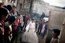 Beduínská svatba ve vesnici Al-Maslach jižně od Gazy: dvanáctiletá prodavačka květin Hasna Abú Wakíd se řadí do průvodu, který ji doprovodí k ženichovu domu. Svatby jsou dodnes slavnostní veřejné udál