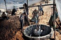 Majitel nového tunelu (v bílé čapce) sleduje, jak se jeho syn spouští do šachty, kde bude pokračovat v kopání. Bohatí majitelé si mohou dovolit mechanický rumpál, tento muž se však musí spolehnout na