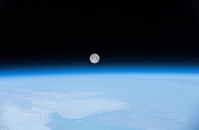 Měsíc, taneční partner Země, vyfotografovaný z Mezinárodní vesmírné stanice vykukuje nad rozostřenou modrou vrstvou atmosféry.