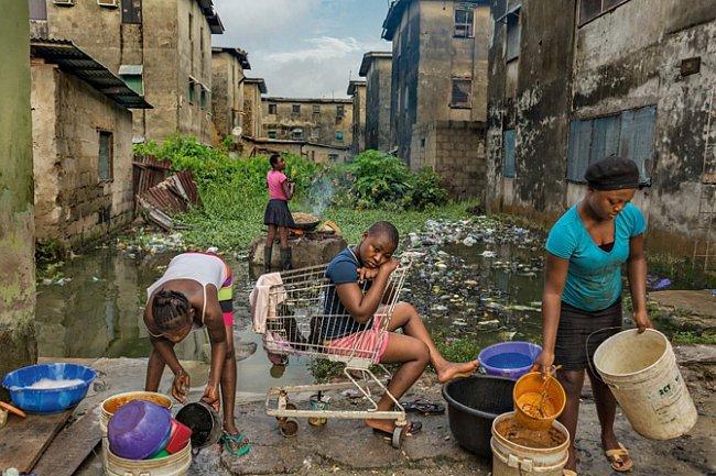 Dívky myjí nádobí avaří burské oříšky (nahoře) naprodej. Pracují vchátrajícím obytném komplexu, jednom zmnoha okrsků laciného bydlení, levně postavených vládou státu Lagos před více než třemi desítkami let.