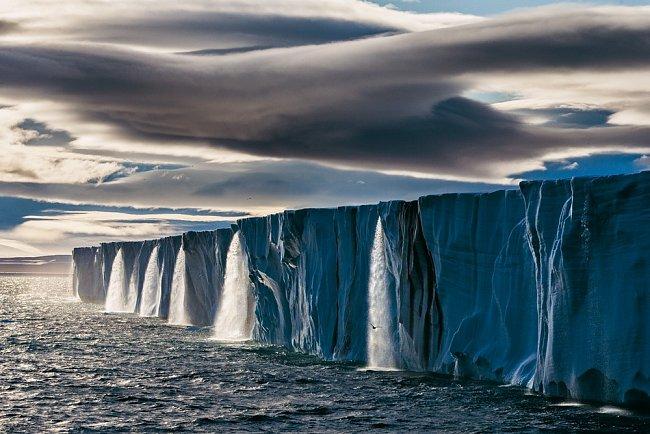 Ztající ledové pokrývky naostrově Nordaustlandet vnorském souostroví Svalbard se řine voda. Arktida se ohřívá rychleji než kterékoli jiné místo naZemi. Led by mohl během léta zcela zmizet ještě vtomto století.
